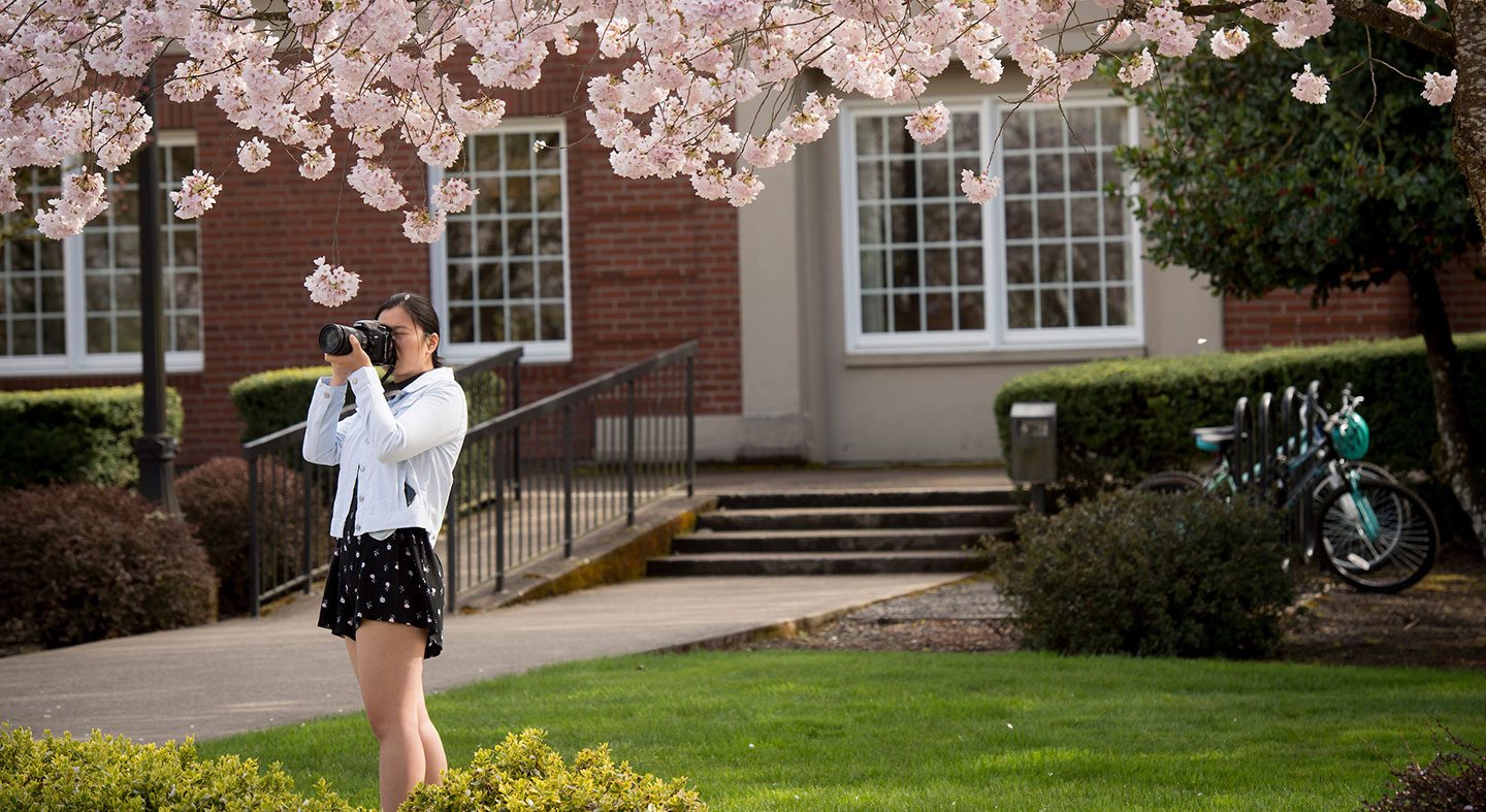 student photographing campus in spring bloom